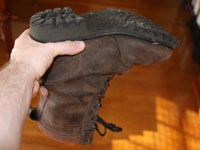 A hand holding a brown work-boot upside down.